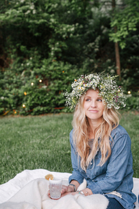 Smiling woman with a flower wreath in her hair sitting in a garden.の写真素材 [FYI02254467]