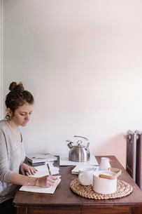 Woman sitting at a table in her apartment, writing in a diary, morning routine.の写真素材 [FYI02254486]