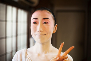 Geisha woman with traditional white face makeup and heavy eyeliner holding up two fingers in a moderの写真素材 [FYI02254494]