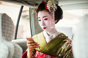 A woman dressed in the traditional geisha style, wearing a kimono and obi, with an elaborate hairstyの写真素材 [FYI02254517]