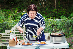 Woman standing at a camping table, preparing two plates of food.の写真素材 [FYI02254519]