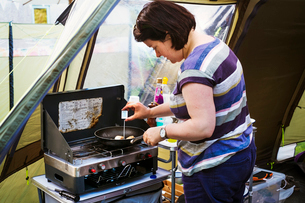 Woman standing at a camping stove, measuring the temperature of a scallop in a frying pan with a digの写真素材 [FYI02254520]