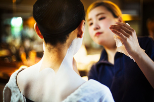 A modern geisha or maiko woman being made up in traditional fashion, with white makeup on her neck aの写真素材 [FYI02254530]