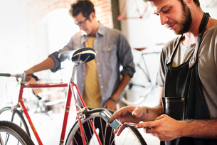 Two men in a cycle repair shop, one holding a smart phone and credit card. Paying by contactless carの写真素材 [FYI02254533]