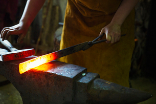 A blacksmith holds a length of red hot metal on an anvil with a pair of tongs.の写真素材 [FYI02254538]