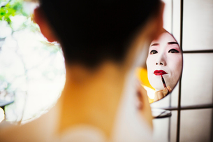 A modern woman creating the traditional geisha vivid red lips by painting on lipstick with a fine brの写真素材 [FYI02254539]