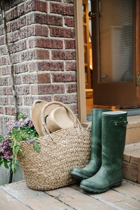 Wellingtons, rubber boots, basket and straw hat by a doorway.の写真素材 [FYI02254556]