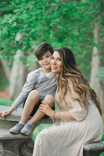 Portrait of a smiling mother and son sitting in a garden.の写真素材 [FYI02254564]