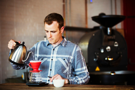 Specialist coffee shop. A man brewing coffee using a filter paper, and drinking it.の写真素材 [FYI02254567]