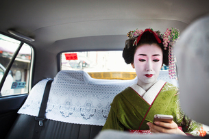 A woman dressed in the traditional geisha style, wearing a kimono with an elaborate hairstyle and flの写真素材 [FYI02254571]