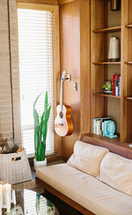 Interior view of a living room with sofa, coffee table, bookcase and an acoustic guitar hanging on aの写真素材 [FYI02254583]