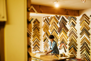 Woman working at a picture framers, a large selection of frames on the walls.の写真素材 [FYI02254586]