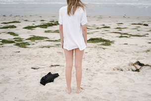 Rear view of a girl with blond hair in a white t-shirt, standing on a sandy beach.の写真素材 [FYI02254588]