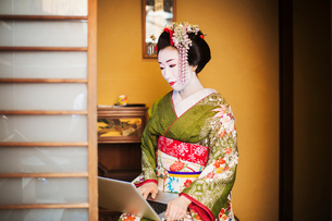 A woman dressed in the traditional geisha style, wearing a kimono and obi, with an elaborate hairstyの写真素材 [FYI02254603]