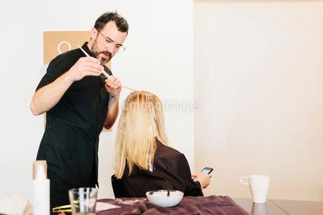 A hair colourist working with foils to give a client with long blonde hair highlights and lowlightsの写真素材 [FYI02254606]