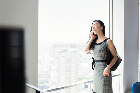A business woman by a window with a view over the city, using her smart phone.の写真素材 [FYI02254610]