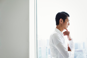 A businessman in the office standing by a large window with arms folded, looking over the city.の写真素材 [FYI02254613]
