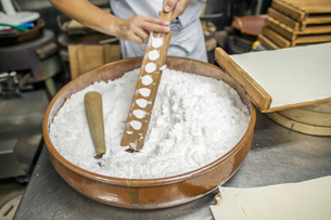 A small artisan producer of wagashi. A man mixing a large bowl of ingredients and pressing the mixedの写真素材 [FYI02254614]