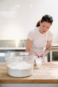 Woman wearing a white apron standing at a work counter in a bakery, measuring flour.の写真素材 [FYI02254617]