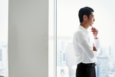 A businessman in the office standing by a large window with arms folded, looking over the city.の写真素材 [FYI02254623]