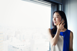 A business woman using her smart phone and standing by a window.の写真素材 [FYI02254640]