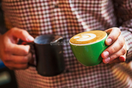 Specialist coffee shop. A man with a cup of fresh made coffee.の写真素材 [FYI02254650]