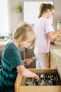 Family preparing breakfast in a kitchen, boy getting cutlery from a drawer.の写真素材 [FYI02254651]