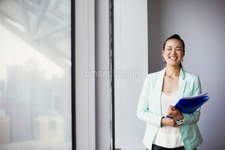 A business woman in the office holding a folder and smiling.の写真素材 [FYI02254652]