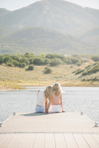 Portrait of two blond sisters sitting on a jetty.の写真素材 [FYI02254658]