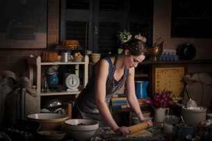 Valentine's Day baking, young woman standing in a kitchen, preparing dough for biscuits.の写真素材 [FYI02254693]