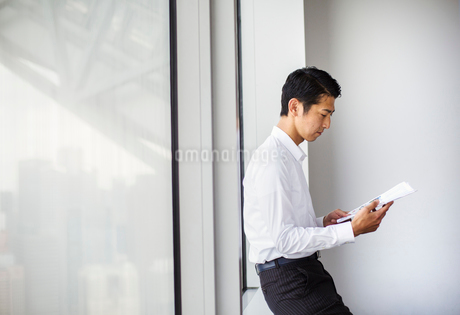 A businessman in the office, by a large window reading paperwork.の写真素材 [FYI02254700]