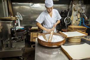 A small artisan producer of wagashi. A man mixing a large bowl of ingredients and pressing the mixedの写真素材 [FYI02254708]