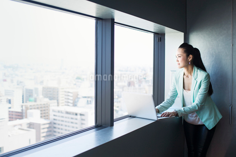 A business woman by a window with a view over the city, looking out. Laptop.の写真素材 [FYI02254712]
