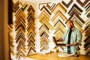 Man working at a picture framers, a large selection of frames on the walls.の写真素材 [FYI02254716]
