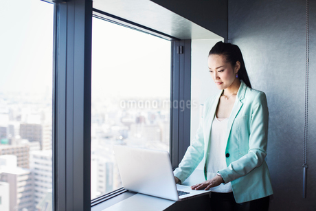 A business woman by a window using her laptop.の写真素材 [FYI02254722]