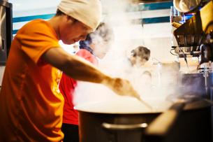 The ramen noodle shop. A chef stirring a huge pot of noodles cooking.の写真素材 [FYI02254734]