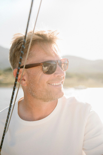 Portrait of a blond man with sunglasses on a sail boat.の写真素材 [FYI02254767]