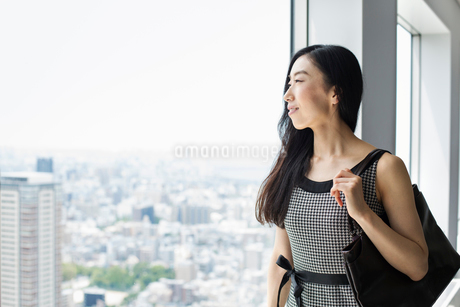 A business woman by a window with a view over the city,の写真素材 [FYI02254768]
