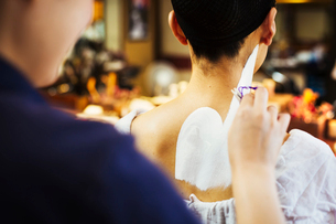 A geisha or maiko with a hair and make up artist, having her neck and shoulders painted in traditionの写真素材 [FYI02254793]
