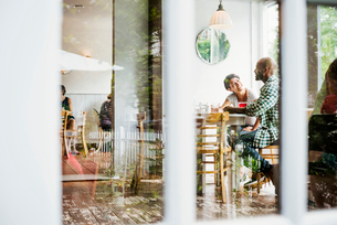 View through a window into a cafe, people sitting at tables.の写真素材 [FYI02254797]