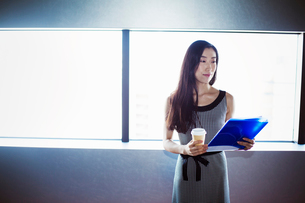 A business woman by a window with a view over the city, holding a cup of coffee and a folder.の写真素材 [FYI02254820]