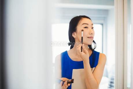 A business woman preparing for work, doing her make up.の写真素材 [FYI02254836]