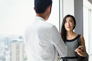 A businessman and businesswoman standing talking by a large window with view over a cityの写真素材 [FYI02254838]
