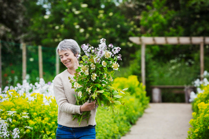 A florist selecting flowers and plants from the garden to create an arrangement. Organic garden.の写真素材 [FYI02254839]