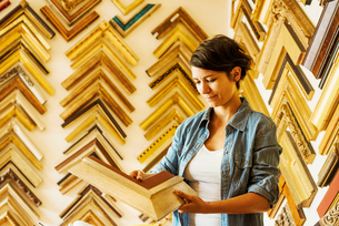Woman working at a picture framers, a large selection of frames on the walls.の写真素材 [FYI02254843]