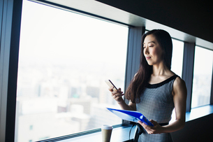 A business woman by a window with a view over the city, using her smart phone.の写真素材 [FYI02254859]