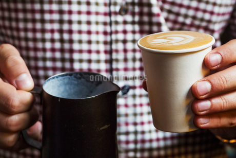 Specialist coffee shop. A person holding a fresh cup of coffee.の写真素材 [FYI02254861]
