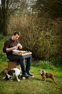 Chef sitting outdoors, preparing seafood, two dogs at his feet.の写真素材 [FYI02254864]