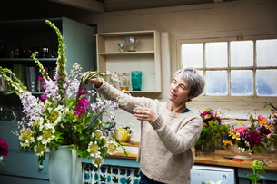 A florist working on a tall vase arrangement of flowers.の写真素材 [FYI02254876]
