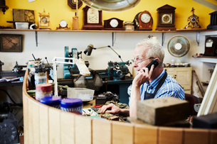 A clock maker on the phone in his workshop.の写真素材 [FYI02254889]
